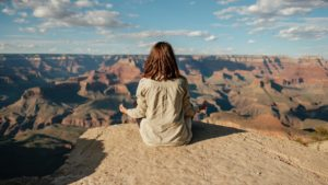Woman sitting on a hill meditating